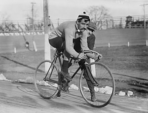 A black-and-white picture of a man on an old bicycle. Another man is holding or pushing the bicycle.