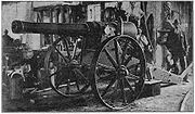 """The """"Long Cecil"""" gun in the workshops of the De Beers company showing a large gun on a carriage with a workman casually looking on in the background."""