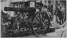 "The ""Long Cecil"" gun in the workshops of the De Beers company showing a large gun on a carriage with a workman casually looking on in the background."