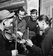 Quebecois lumberjacks playing the fiddle, with sticks for percussion, in a lumber camp in 1943.