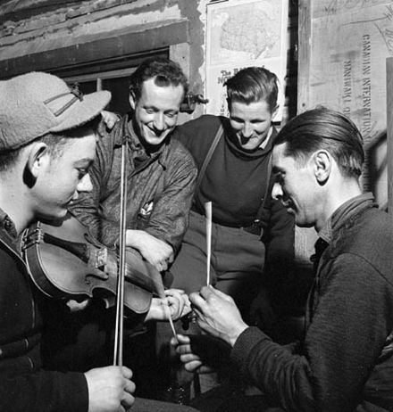 French-Canadian lumberjacks playing the fiddle, with sticks for percussion, in a lumber camp in 1943. Lumbermen violin and sticks 1943.jpg
