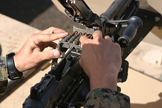 M240 machine gun - A Marine inserts an ammunition belt into the feed tray of the M240G.