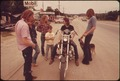 MOTORCYCLIST SHOWING OFF HIS POSSESSION TO HIS FRIENDS IN LEAKEY, TEXAS, NEAR SAN ANTONIO - NARA - 554871.tif