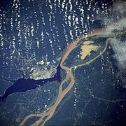 Manaus, the largest city on the Amazon, as seen from a NASA satellite image, surrounded by the muddy Amazon River and the dark Rio Negro.