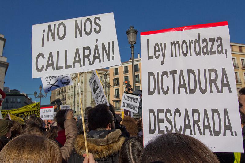 https://upload.wikimedia.org/wikipedia/commons/thumb/9/94/Manifestaci%C3%B3n_contra_la_Ley_Mordaza_en_Madrid_20-12-2014_-_19.jpg/800px-Manifestaci%C3%B3n_contra_la_Ley_Mordaza_en_Madrid_20-12-2014_-_19.jpg