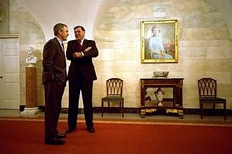 Mel Martínez - Senator Mel Martínez chats with U.S. President George W. Bush in the Center Hall of the White House during a celebration of Cinco de Mayo. The official portrait of former First Lady Betty Ford can be seen on the wall.