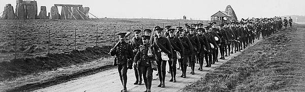 Men in uniform walking past Stonehenge, old picture