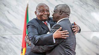 Afonso Dhlakama - Dhlakama (right) ratifying a 2014 peace deal with Mozambique's President Armando Guebuza.