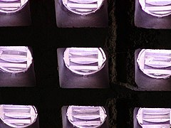 View from below of small circular panes of translucent lavender glass, deeply set in a coffered grid. Each circle has three parallel pendant-prism ridges.
