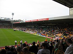 The inside of an association football stadium, with a stand on the right-hand side full of supporters. The pitch is visible to the left of the stand, with a floodlight in the background.
