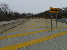 A freeway coming to a blocked-off dead end in a wooded area, with a right arrow sign pointing motorists onto an off-ramp