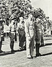Full-length, three-quarter-angle, outdoor portrait of half a dozen or so men in light tropical military uniforms with headgear, standing to attention. Two of the men are in the foreground and the rest in a row behind them.