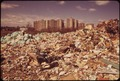 OVERFLOWING CITY DUMP IS AN OFFENSE TO THE RESIDENTS OF CO-OP CITY (HOUSING DEVELOPMENT IN BACKGROUND) - NARA - 549739.tif