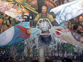 The central scene. A workman is depicted controlling machinery. Before him, a giant fist emerges holding an orb depicting the recombination of atoms and dividing cells in acts of chemical and biological generation.