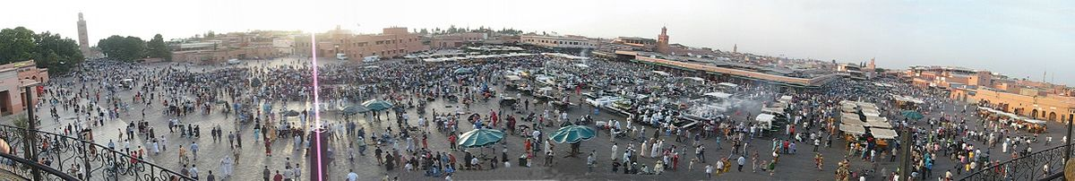 Panoramic picture of the Djemaa el Fna square at sunset. Koutoubia Mosque appears on the extreme left. The souks are in the alleys behind the square