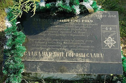 "World War II-era monument in memory of UPA fighters with inscription ""Glory to Ukraine! Glory to the heroes!"", in place of the Janowa Dolina massacre, Bazaltove, Ukraine Pomnik UPA w Bazaltowe d.Janowa Dolina.jpg"