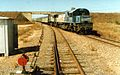 QR loco 1556 and a 1720 class haul the Sunlander northbound through Yabulu, ~1991.jpg