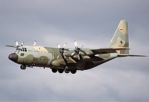 Colour photo of a four-engined aircraft painted in a camouflage pattern