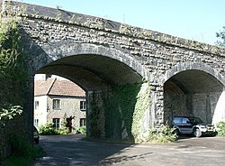 Two arches of a stone and brick bridge with a car beneath.