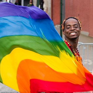 English: A man with a rainbow flag at the Gay ...