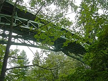 A steel-arched bridge over a wooded ravine