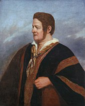 """Half-length painted portrait of a clean-shaven, auburn-haired man with long sideburns and wearing a black poncho with bands embroidered in red and gold"""