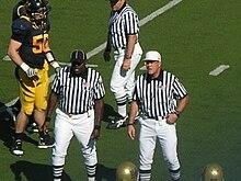 Un referee (col berretto bianco) annuncia le decisioni arbitrali.