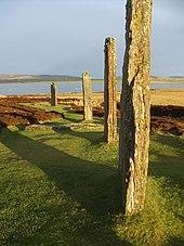 Quatre grandes pierres dressées se trouvent dans un champ d'herbe et de bruyère.  Ils sont éclairés par la lumière du soleil rougeâtre et ils projettent de longues ombres vers la gauche.  Un lac et de basses collines se trouvent au-delà.
