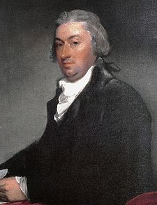 An oil portrait of a clean-shaven older man, seated, wearing a black robe and white neck ruff