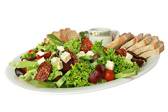 Salad - A garden salad consisting of lettuce, cucumber, scallions, cherry tomatoes, olives, sun-dried tomatoes, and cheese