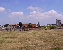 Landscape photo dominated by a field in front, surmounted by blue sky with white clouds. A row of modern buildings crosses the center; in front of the buildings a few stones can be seen piled atop each other.