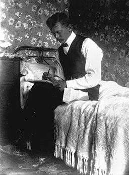 StateLibQld 2 171951 Intimate portrait of a man writing a letter, 1900-1910