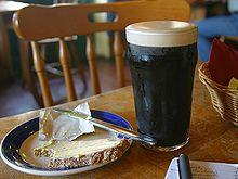 Una pinta di birra stout con una fetta di pane e burro