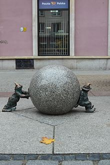 Sisypher dwarves sculpture by Tomasz Moczek. Two small bronze figures stand either side of a stone sphere.