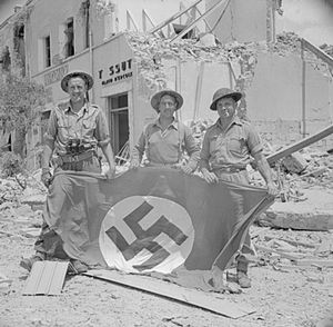 Reconnaissance Corps - Men of the 1st Reconnaissance Regiment, part of the 1st Infantry Division, pose with a captured German swastika flag in Littoria, Italy, 25 May 1944. They are, from left to right: Corporal H. Seddon, Trooper R. Carslake and Trooper J. Callaghan.