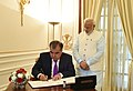 The President of the Republic of Tajikistan, Mr. Emomali Rahmon signing the visitor's book, at Hyderabad House, in New Delhi on December 17, 2016. The Prime Minister, Shri Narendra Modi is also seen.jpg