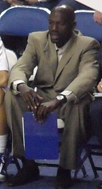 An African-American man sitting and wearing a tan suit