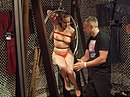 Topless woman bound to a ring at BoundCon 2015.jpg