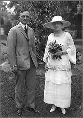 Liganta foto de Truman en griza vestokompleto kaj lia edzino en ĉapelo kun blanka robposedo floras