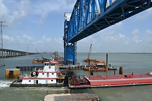 Galveston Causeway - A barge passing under the new lift span on the railroad causeway, with the 2008-opened new causeway for road vehicles visible at left
