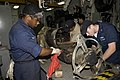 US Navy 060330-N-2420K-009 Electrician's Mate Fireman David Benjamin and Petty Officer 2nd Class Justin Russell, clean grime off the arbor of an electric generator.jpg