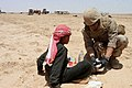 US Navy 080606-M-3663L-119 A U.S Navy Corpsman assigned to Charlie Co. of Marine Wing Support Squadron 27, Marine Air Group 37, gives medical care to an Iraqi child in the Al Anbar province.jpg