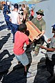 US Navy 080922-N-7955L-078 U.S. service members assigned to the amphibious assault ship USS Kearsarge (LHD 3) and Haitian civilians move boxes of cooking oil during a humanitarian assistance mission to aid Haitians affected by.jpg