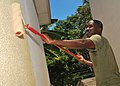 US Navy 100302-N-8463W-088 Kenyan navy 2nd Lt. Gavin Kasyoka paints the main building of the Foyer De Nazareth.jpg