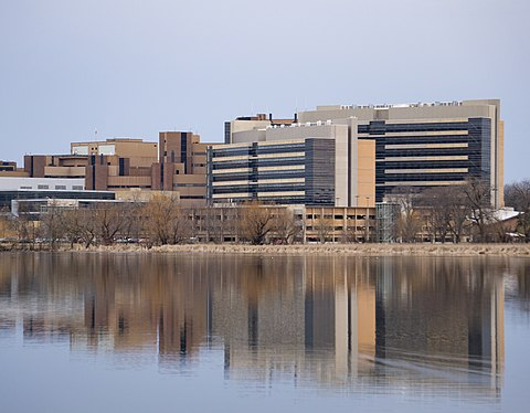 A view of UW Health University Hospital, the Health Sciences Learning Center (HSLC), and the Wisconsin Institutes for Medical Research rising above Lake Mendota, on the western edge of the UW-Madison campus. The University of Wisconsin School of Medicine and Public Health, housed in the HSLC, accounts for 40% of UW-Madison's research grants UW Health and UWSMPH.jpg