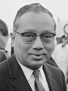 Chân dung chính thức của U Thant trên nền hiệu kỳ Liên Hiệp Quốc.