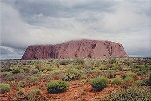 Der Uluru fahlbraun mit wolkenverhülltem Gipfelplateau (Blick von Nordwesten).