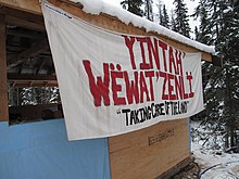 "A banner with the words YINTAH' WËWAT'ZENLÏ in red and beneath, the words ""TAKING CARE OF THE LAND"" in black"