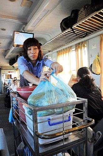 Food cart - Vietnam Railways employee sells corn from a cart