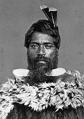 Man wearing traditional Māori cloak with two feathers in his hair